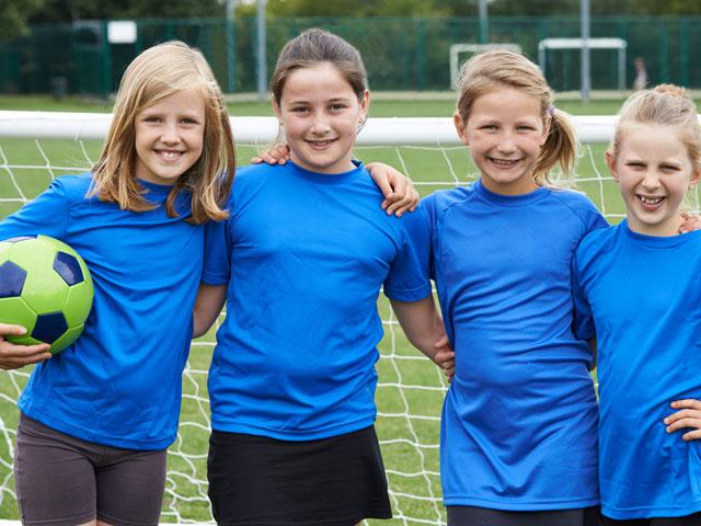 groupe d'enfants souriants en stage sportif de football féminin