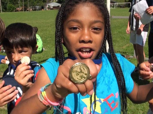Fillette fière de montrer sa médaille de football féminin pendant un stage sportif pendant les vacances scolaires d'été