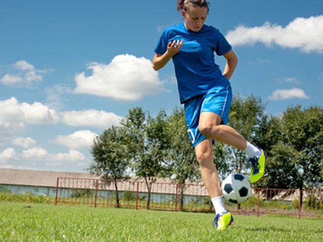 Adolescente s'entrainant au football féminin en stage sportif cet ét