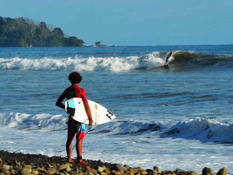 Adolescent avec sa planche de surf au Costa rica en colo