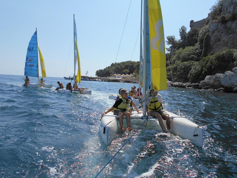 Enfants faisant de l'optimist en colonie de vacances à la mer