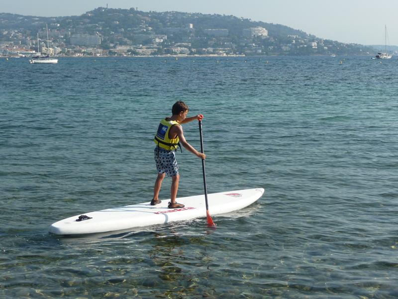 Enfant de 12 ans faisant du stand up paddle en colonie de vacances à la mer