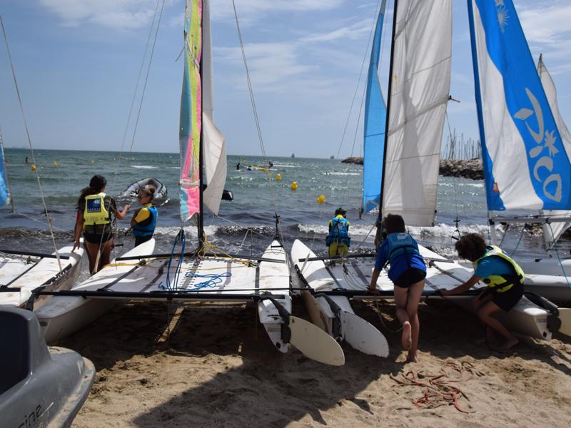 Enfants montant sur un bateau en colonie de vacances à la mer
