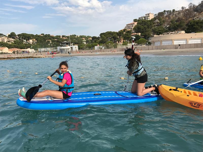 Deux jeunes filles apprenant à faire du canoe kayak en colonie de vacances