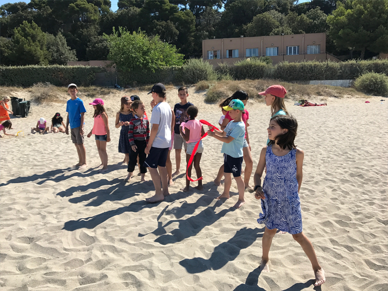 Enfants jouant sur la plage en colo à la mer