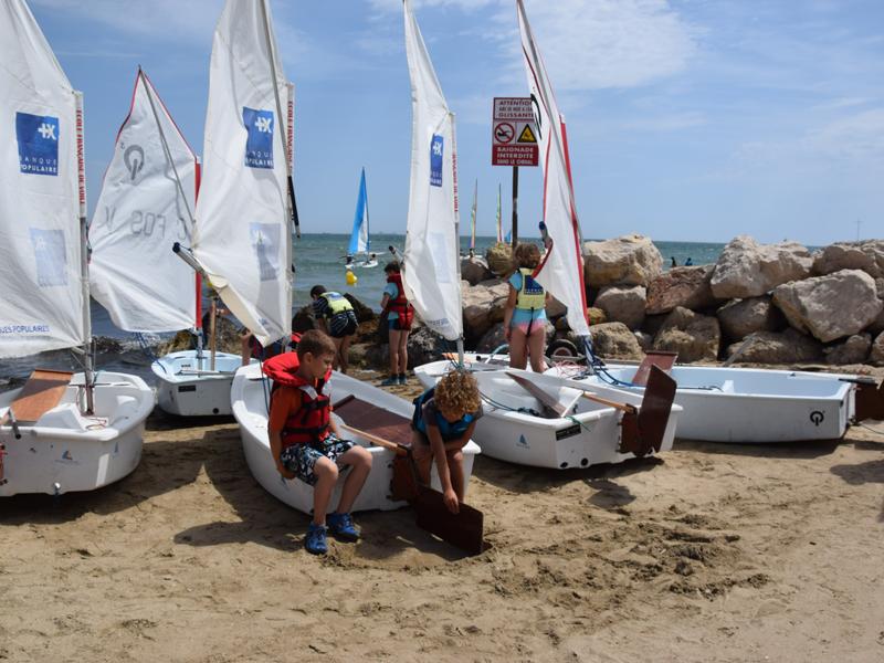 Groupe d'enfants sur la plage s'apprêtant à faire de l'optimist en colonie de vacances