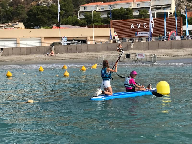 Jeune fille apprenant à faire du stand up paddle en colonie de vacances à la mer