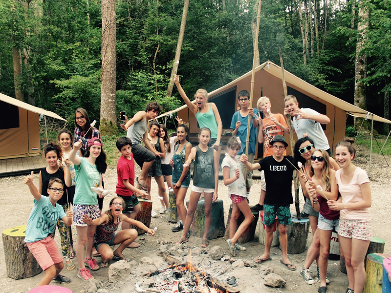 Groupe d'enfants autour d'un feu de camp en colonie de vacances cet été