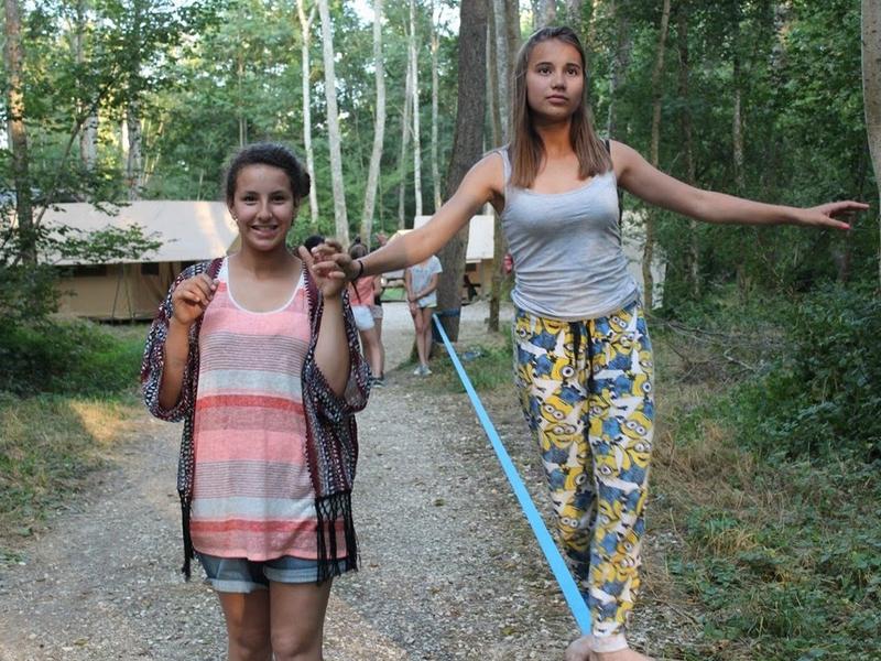 Deux jeunes filles faisant du slackline en colo d'été