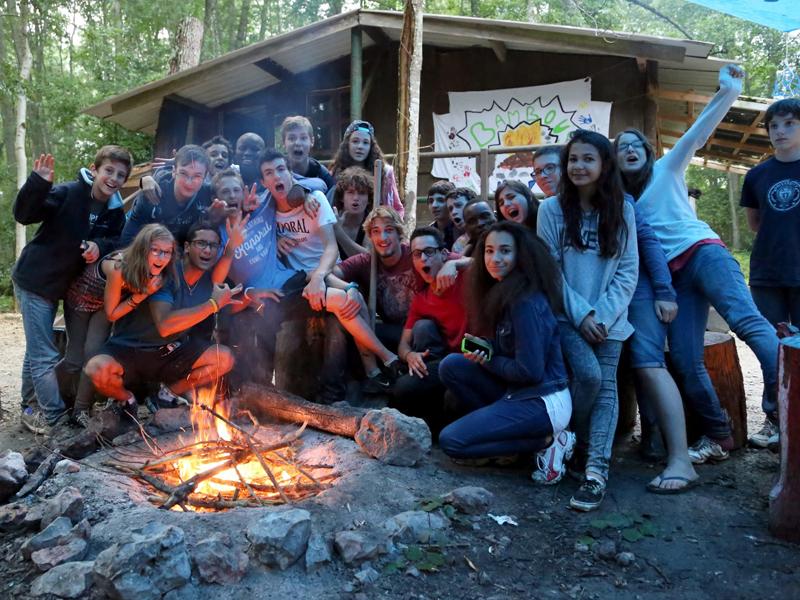 groupe d'ados et enfants autour d'un feu de camp en colo