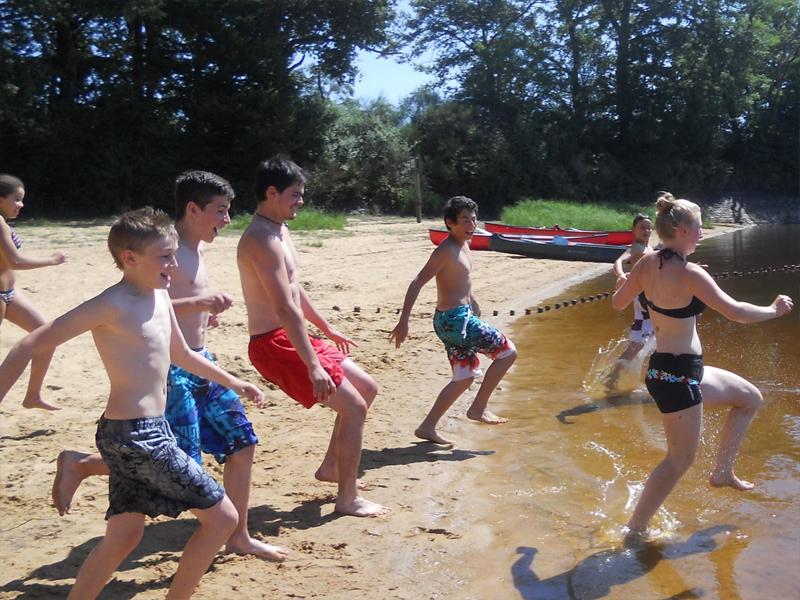 groupe d'ados courant dans l'eau en colo cet été