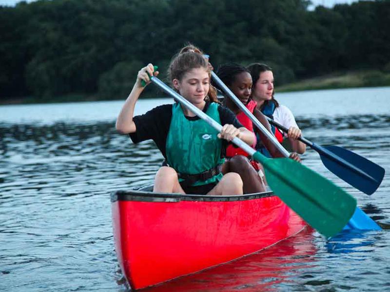adolescentes faisant du canoe kayak en colonie de vacances