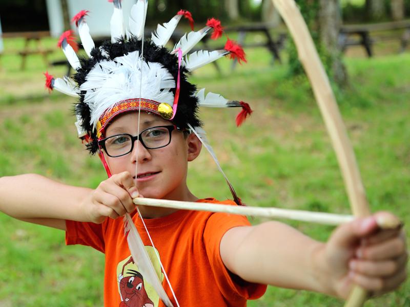 Enfant portant une coiffe d'indien apprenant à faire du tir à l'arc en colonie de vacances