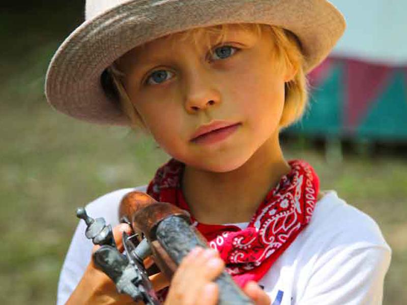 Portrait d'un petit garçon déguisé en cow boy cet été en colonie de vacances au far west