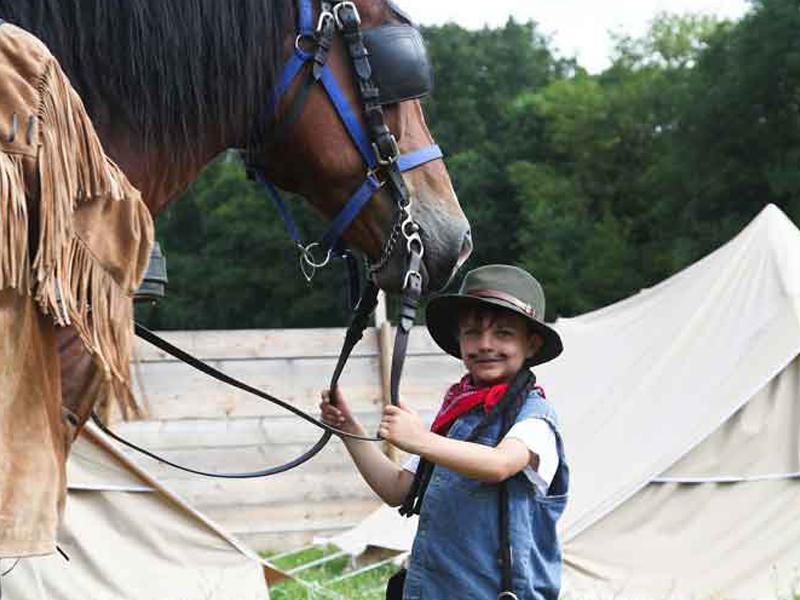 Jeune garçon avec un chapeau de cow boy s'occupant de son cheval en colo