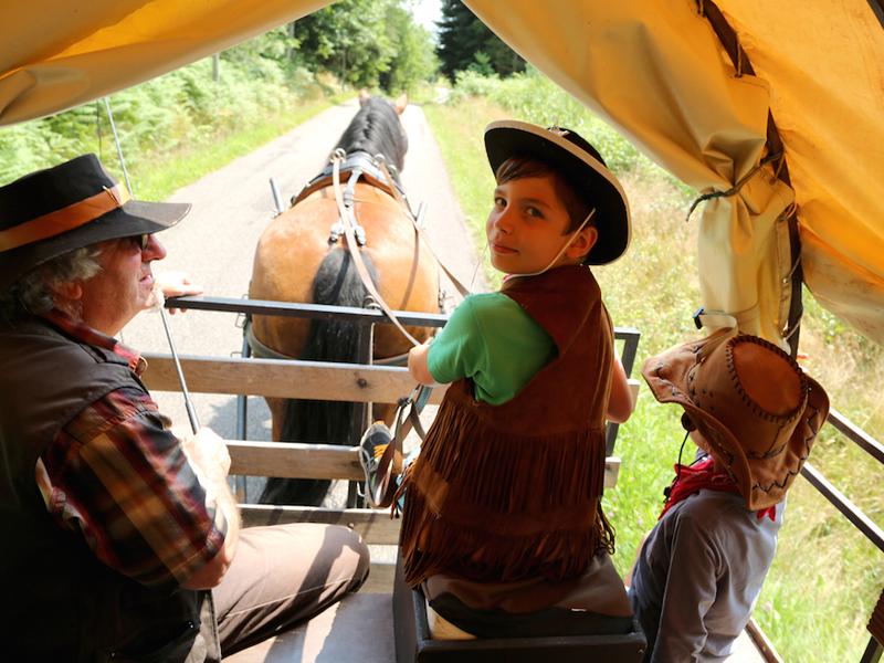Enfants à l'intérieur d'une carriole en colonie de vacances far west
