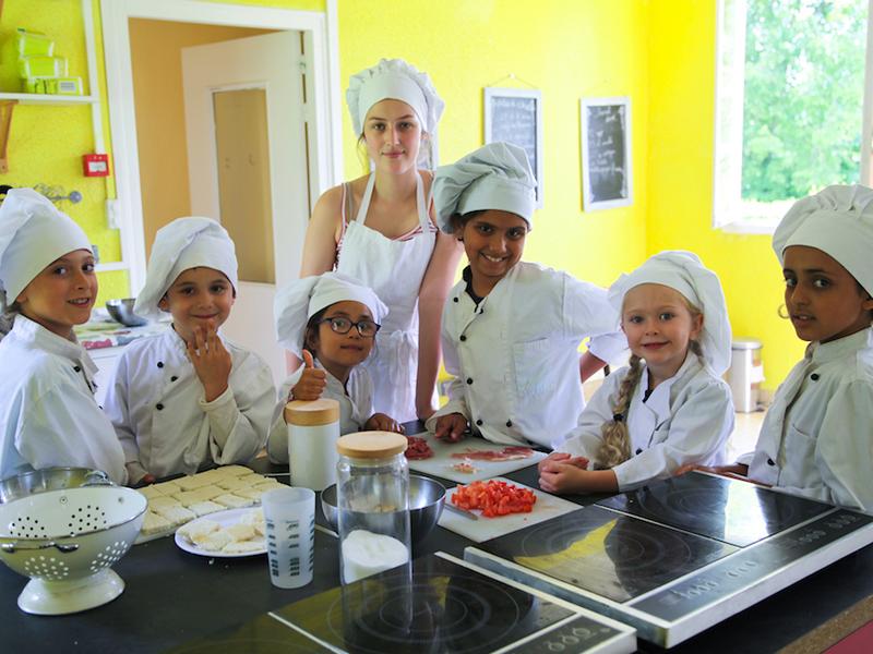 enfants apprenant à faire la cuisine en colonie de vacances