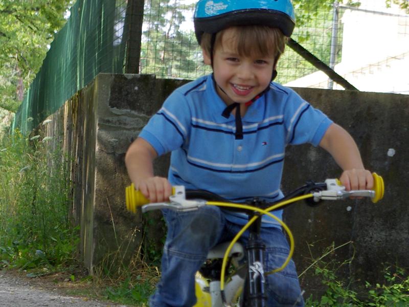 Enfant à vélo en colonie de vacances à la ferme cet été