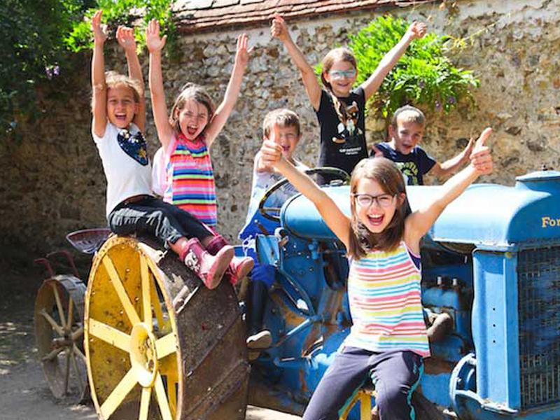 Enfants sur un tracteur en colonie de vacances à la ferme
