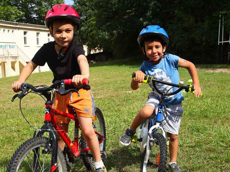 Jeunes enfants à vélo en colonie de vacances à la ferme
