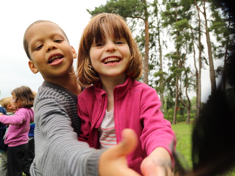Enfants jouant dehors en colo à la ferme cet été