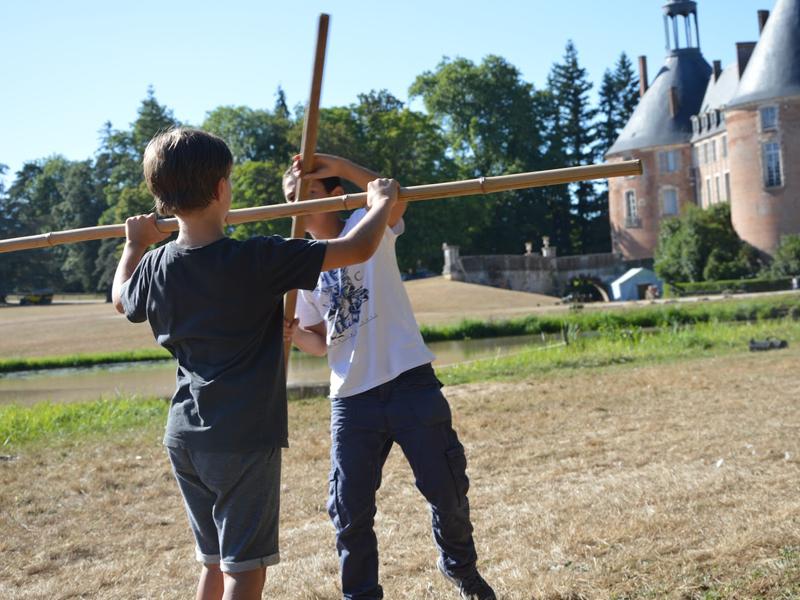Enfants faisant une bataille de batons en colo médiévale