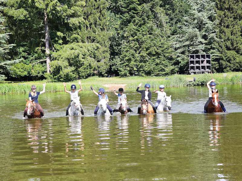 Enfants traversant la rivière à cheval en colonie de vacances moyen age