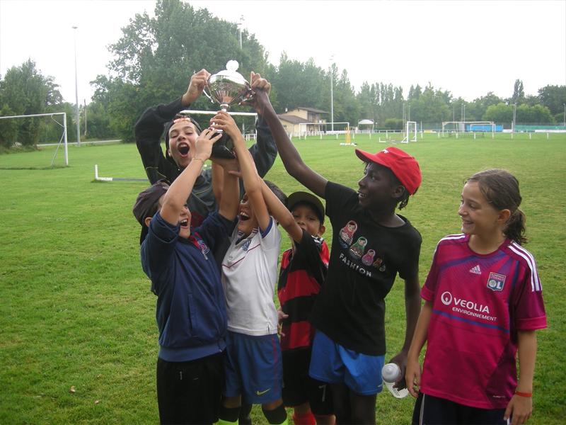 enfants tenant une médaille de foot en colonie de vacances cet été