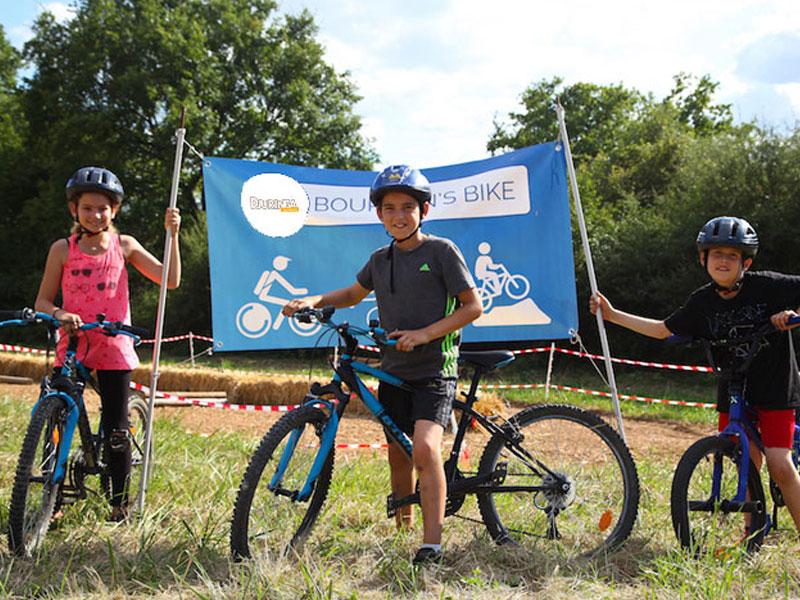 trois enfants au départ d'une course à vélo en colonie de vacances d'été