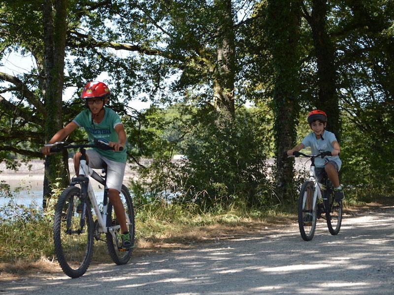 deux enfants faisant du vélo en colonie de vacances cet été