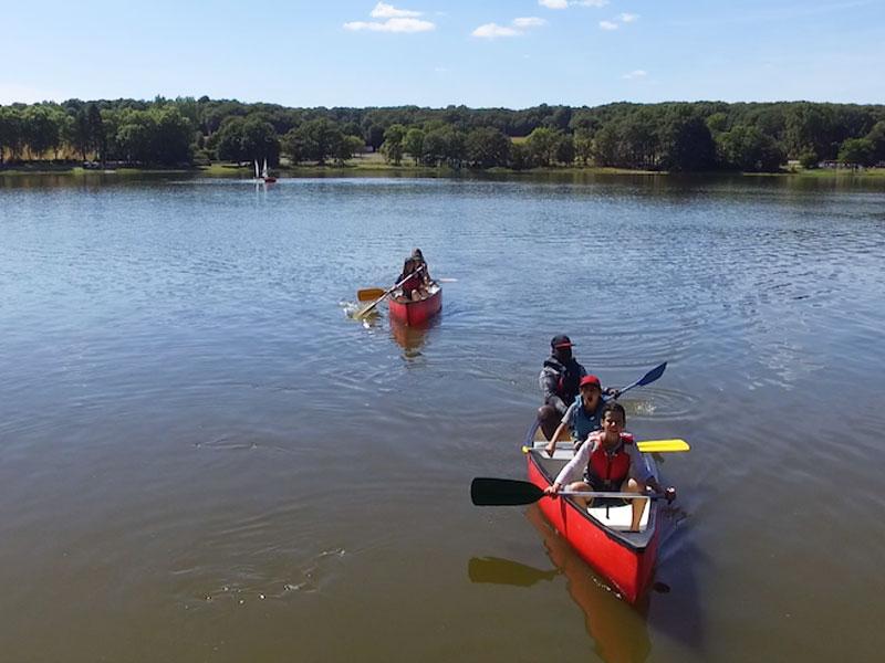 enfants sur un lac en train de faire du canoe en colonie de vacances