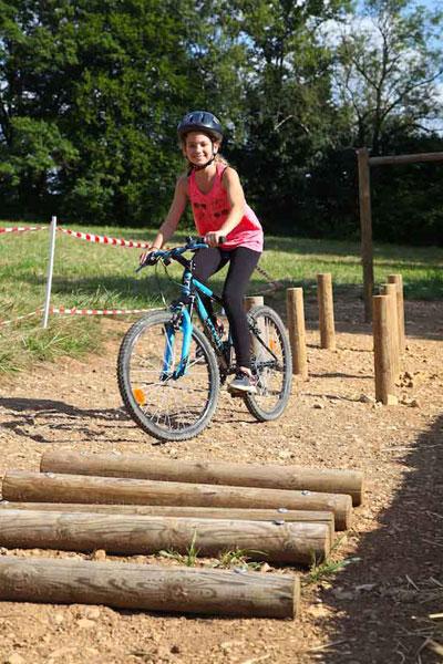 Enfant faisant du vélo en colo cet été