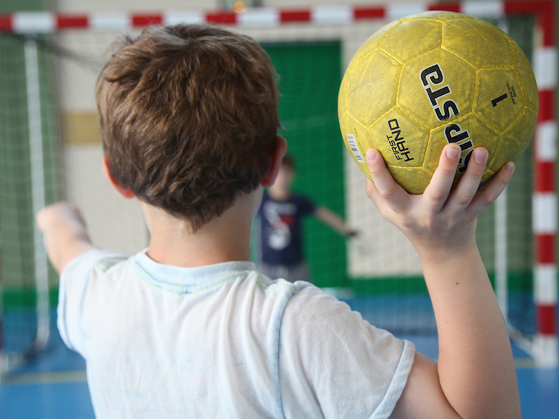 Enfant jouant au handball en colonie de vacances sportive