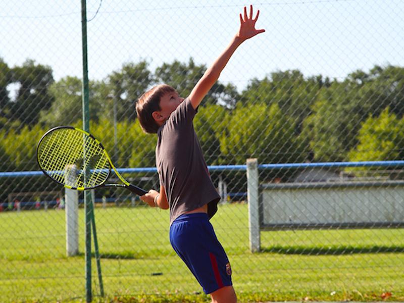 Enfant pratiquant le badminton en colo cet été
