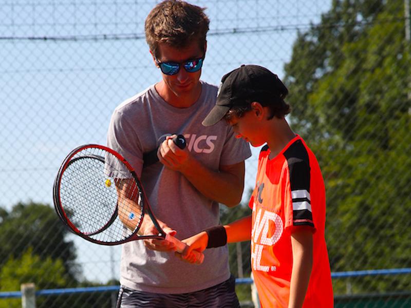 Animateur apprenant à un ado à manier la raquette de tennis