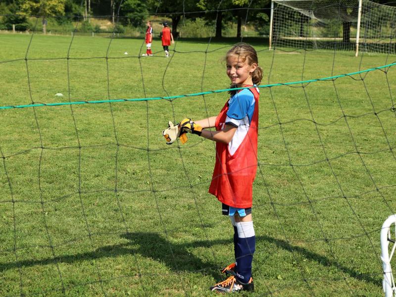 fillette jouant au football cet été en colonie de vacances sportives