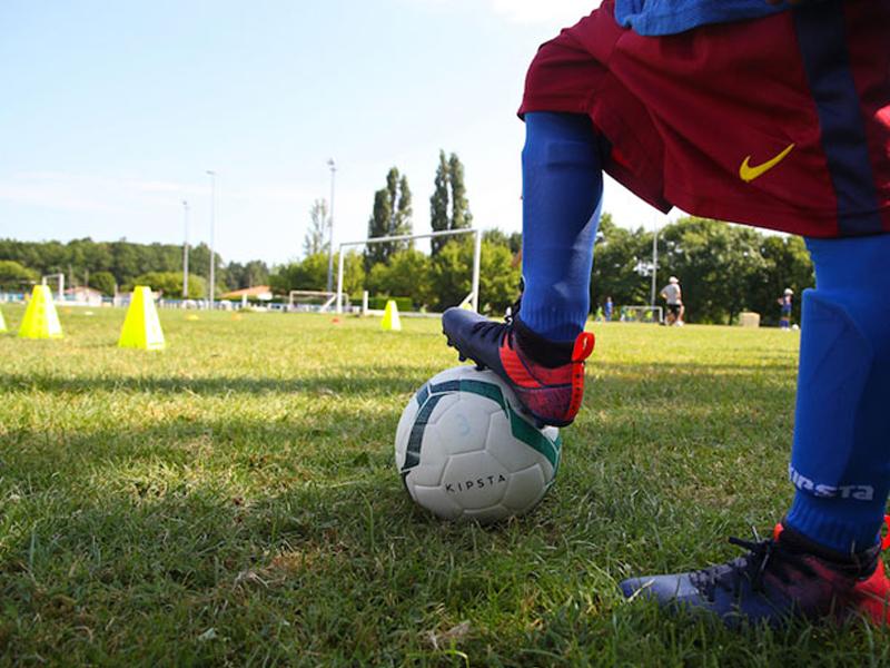 enfant en tenue de football en colonie de vacances sportive