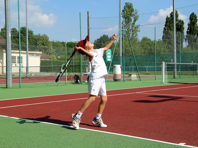 Enfant jouant au tennis en colonie de vacances cet été