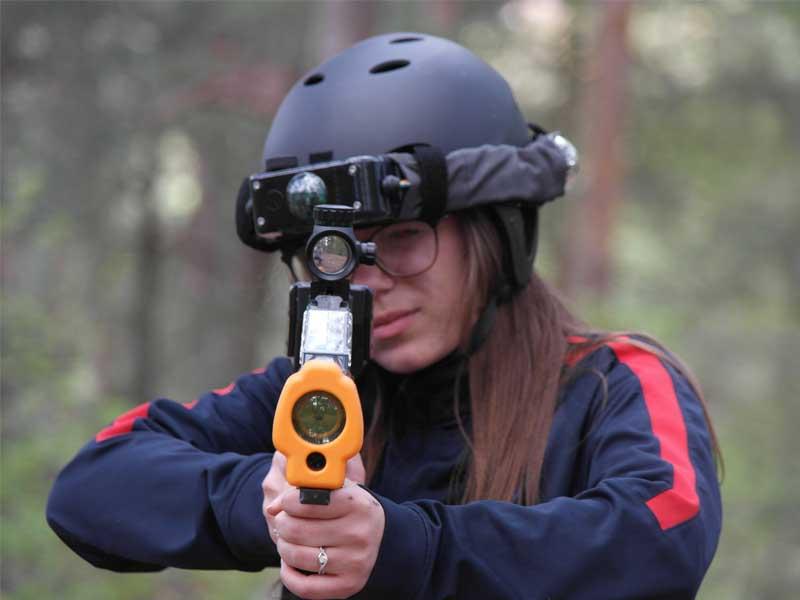 Portrait d'une adolescente visant avec son fusil laser en colonie de vacances laser game extérieur cet été