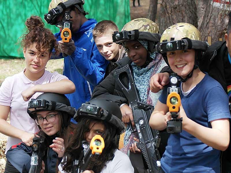 Groupe d'ados et enfants portant des casques et un fusil faisant une partie de laser game extérieur en colonie de vacances d'été