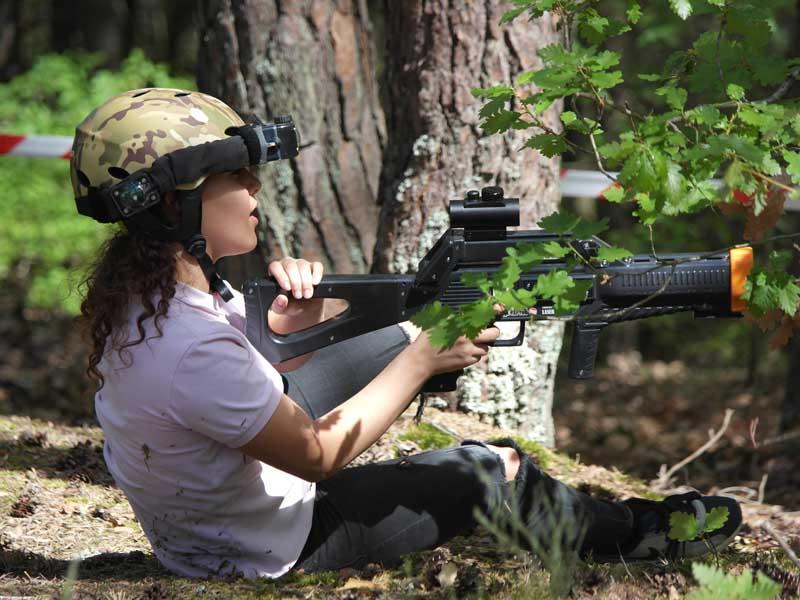 Jeune fille portant un casque dans la forêt avec un fusil laser en pleine partie de lasergame en colonie de vacances été