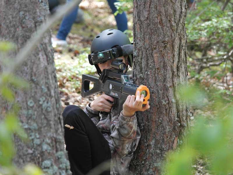 Enfant caché dans la forêt pendant une partie de laser game extérieur en colonie de vacances été