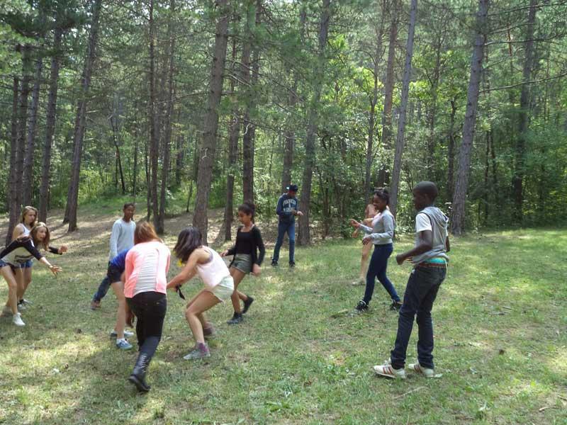 Groupe d'enfants jouant dans la forêt en colonie de vacances cet été
