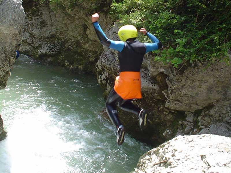 Un jeune saute d'un cascade durant l'activité via ferrata de la colonie de vacances cette été
