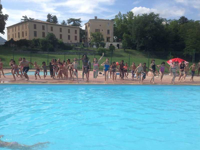 Les jeunes de la colonie de vacances sautent ensemble dans la piscine du centre