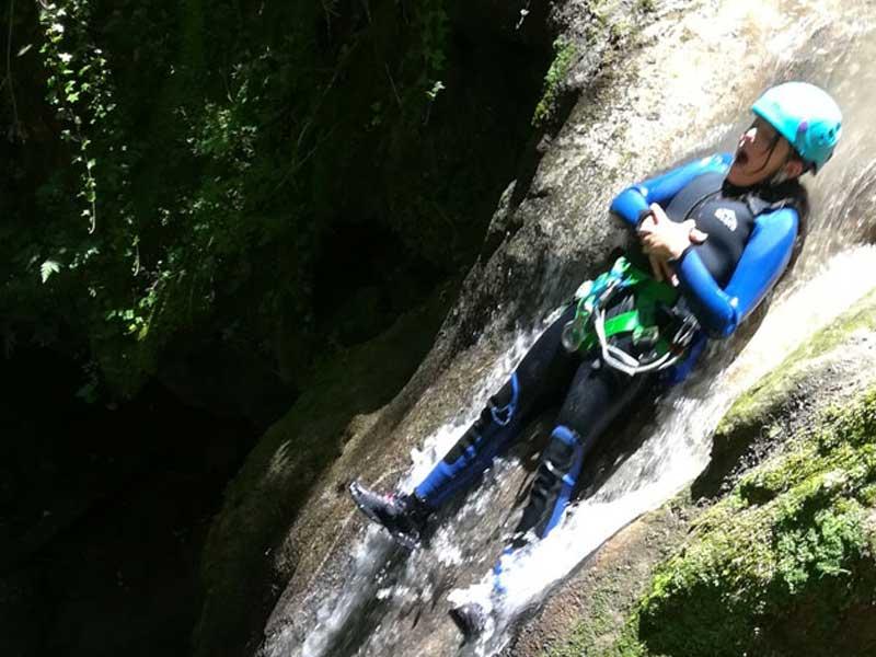 Un jeune de la colo prend un tobogan naturelle durant l'activité via ferrata de la colonie de vacances