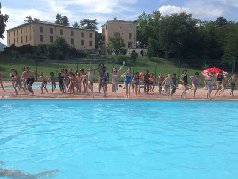 Les enfants de la colonie de vacances sautent tous ensemble dans la piscine