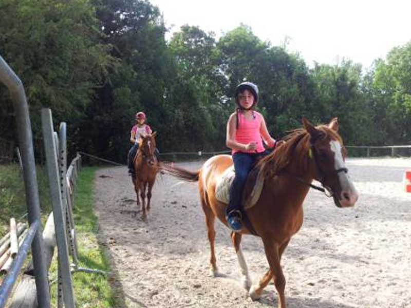 Enfants en colonie de vacances faisant de l'équitation