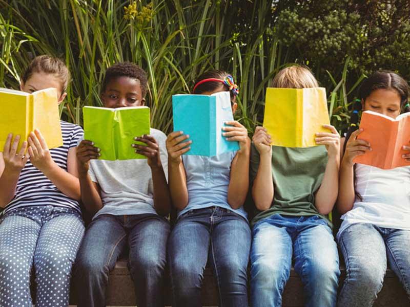 Des enfants en colonie de vacances en train de lire un livre