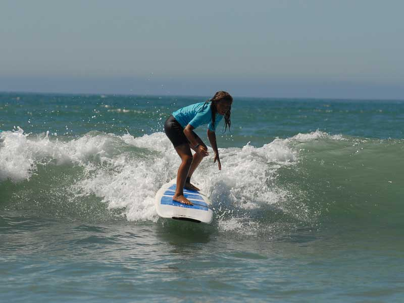 Enfant qui pratique le surf en colonie de vacances